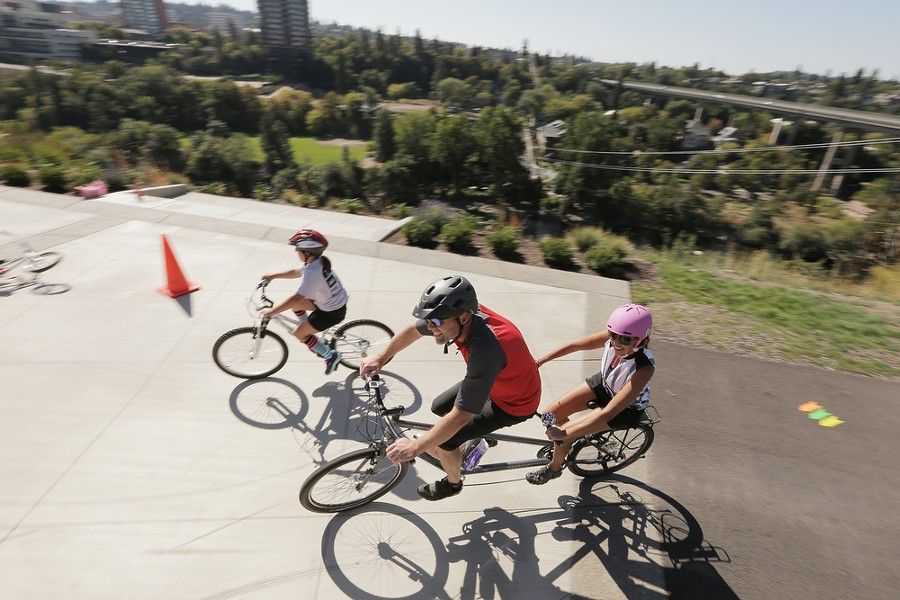 Bicyclists turn from the Centennial Trail to N. Cedar St. - YOUNG KWAK