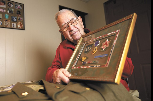 Bill Akers, a private first class during World War II, with his uniform and awards for service. - YOUNG KWAK