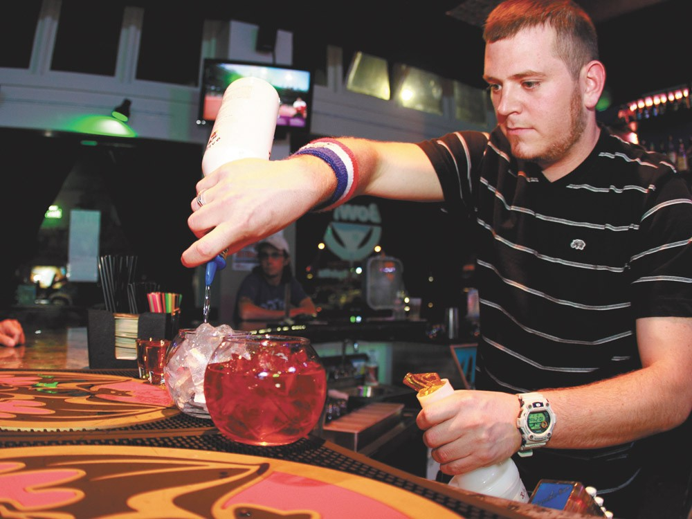 Bowl'z co-founder Jake Miller whips up one of bar's signature drinks. - JOE KONEK