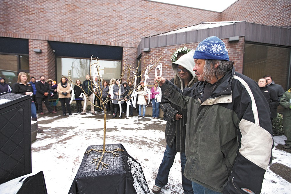 Bruce Geer, right, places a bell representing one of the 39 local homeless people who died this year. - YOUNG KWAK
