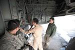 Captain Mike Dobbs, right, checks the wheel well of a KC-135 at Manas, as Senior Airman Nick Stevens looks on.