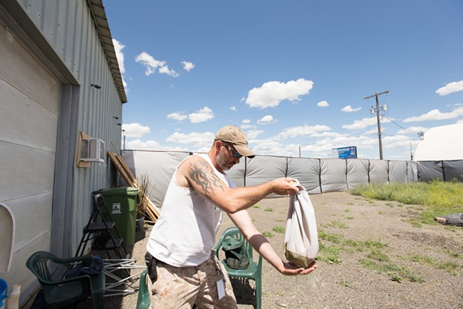 Co-Owner Wesley Tuttle shakes a bag of water before drying the hash contained within. - YOUNG KWAK
