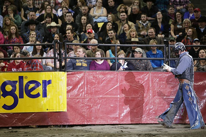 Colby Reilly, of Ephrata, Wash., walks towards an exit chute after riding W1 Buckey, not pictured, during the Championship Round on Saturday. He rode 7.79 seconds before falling off the bull. - YOUNG KWAK