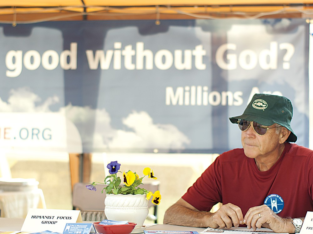 Dick Gammon, member of the Inland Northwest Humanists, reads the Freethought Today newspaper while tending the booth. - MIKE MCCALL