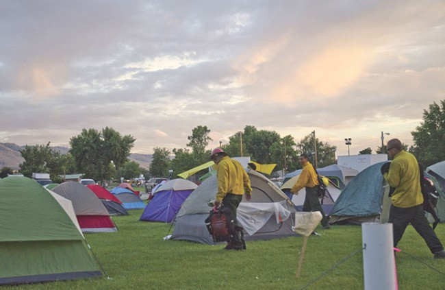 Dozens of tents shelter wildfire crews at a temporary fire camp at the Omak Stampede fairgrounds. - JACOB JONES