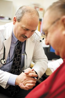 Dr. John Torquato prays with his patient, Gerben Roukema, at the Hayden Family Medical Care clinic. - YOUNG KWAK