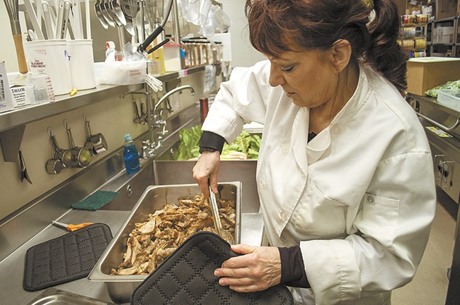 Early in the school day, kitchen lead Pauline Battien prepares pulled pork from scratch.