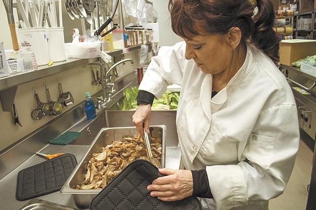 Early in the school day, kitchen lead Pauline Battien prepares pulled pork from scratch.