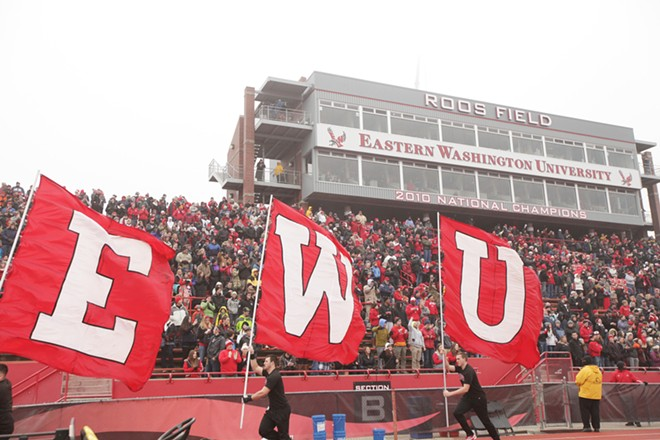 Eastern Washington fans cheer as the EWU flags are carried around the sidelines before the game. - YOUNG KWAK