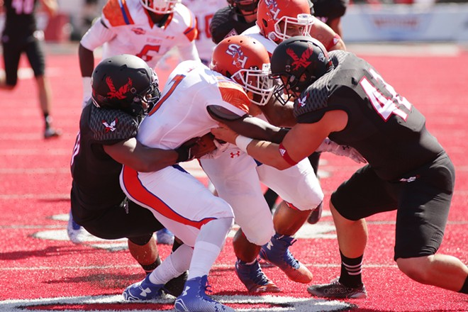 Eastern Washington linebacker Jordan Talley (20), left, and long snapper Cory Alcantar, right, bring down Sam Houston State cornerback Trenier Orr during the first half. - YOUNG KWAK