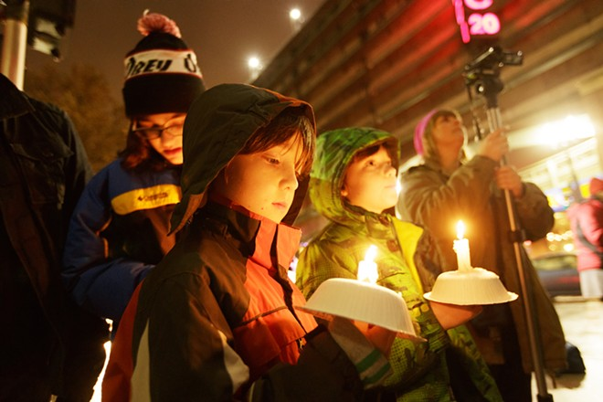 Eight-year-old Jonathan, center, and his 11 year old brother Gabriel, right, hold candles in front of city hall. - YOUNG KWAK