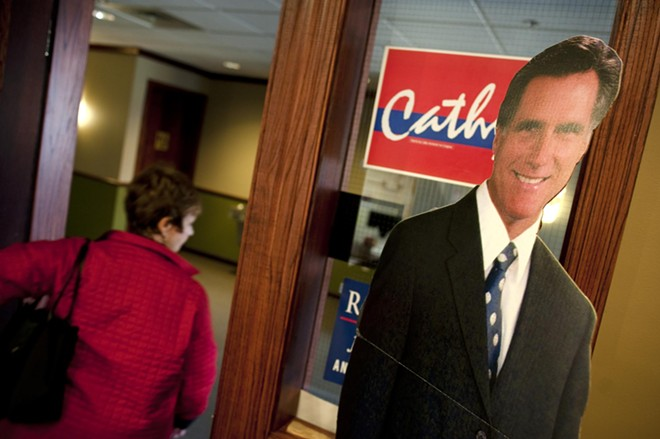 """A volunteer leaves the GOP Victory Center HQ, saying """"What a good looking guy,"""" as she passes a life-size cutout of Mitt Romney."""