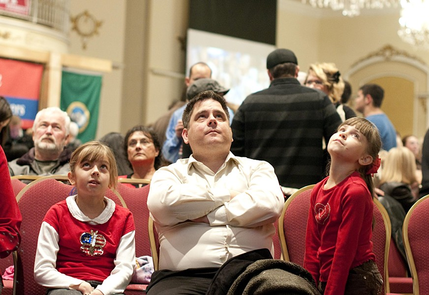 Tom Buck and his daughters Faith (left) and Hannah (right) react to the presidential election results at the McMorris-Rodgers watch party at the Davenport Hotel Tuesday evening.