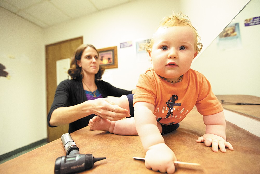 Eleven-month-old Beckett Smith crawls away during an exam with nurse practitioner Brooke Jordan. - YOUNG KWAK