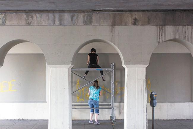 Ellen Picken (top) and Erin Mielcarek (bottom) begin work on their mural on Wall Street. - MATT WEIGAND