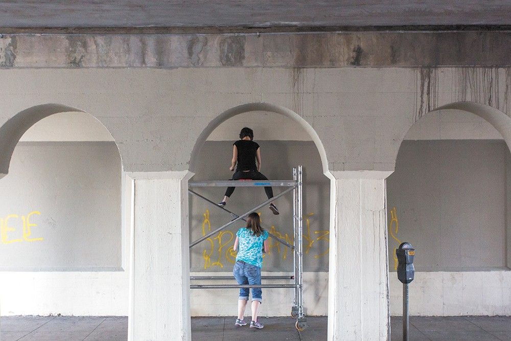 Ellen Picken (top) and Erin Mielcarek (bottom) begin work on their mural on Wall Street. - MATT WEIGAND