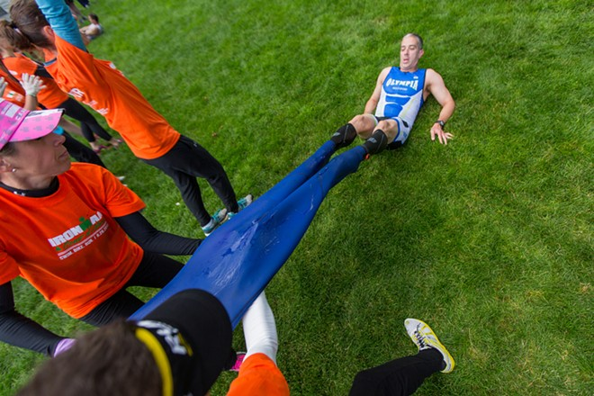 Erica Ziemer, left, pulls off a competitor's wetsuit with another volunteer. - MATT WEIGAND