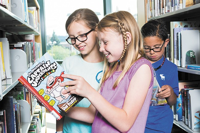 Faith and Addie share a Captain Underpants book at the downtown Spokane Library. - STEPHEN SCHLANGE
