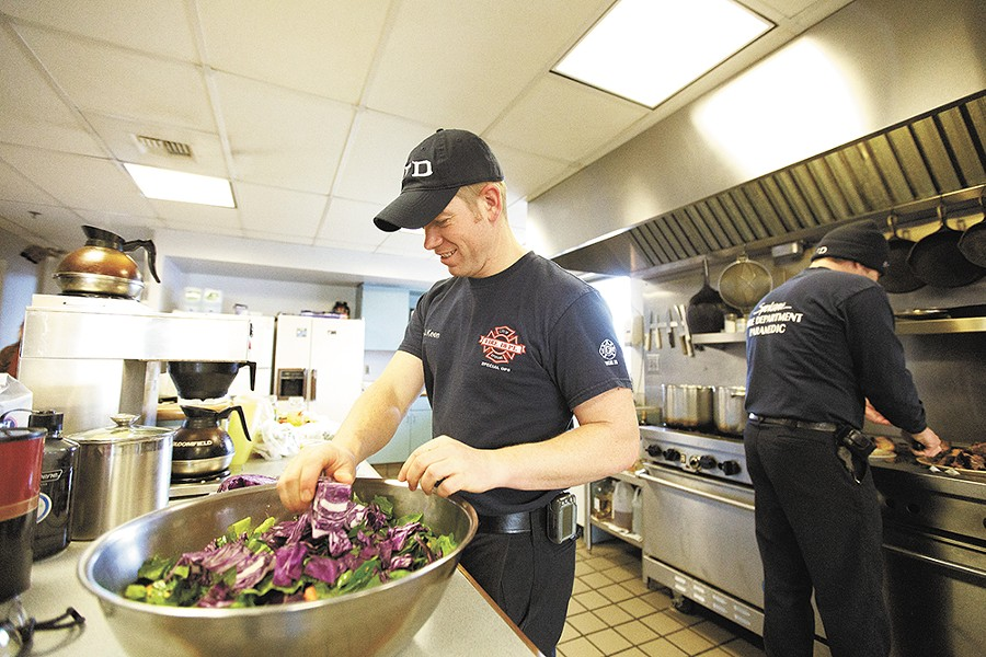 Firefighter Jason Keen (above) keeps it green with a big salad at Spokane Fire Station 2, while Capt. Don Waller (below) digs in. - YOUNG KWAK