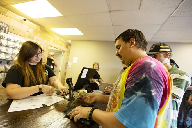 First customer Mike Boyer, right, pays for two grams of Farmer J's Sour Kush from Spokane Green Leaf employee Caitlyn Finger. - YOUNG KWAK