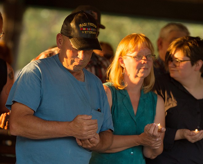 Gary Kennison and his wife, Karri, share a moment of silence for their daughter, Sheena Henderson, and her husband, Chris, at a vigil in their honor. - YOUNG KWAK