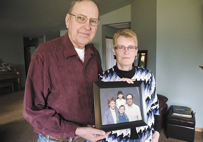 Geri and Sharon Johnson, of Spokane Valley, pose with a family photo of them with their son Aaron, who was shot multiple times by Spokane police on Jan. 16. - JACOB JONES