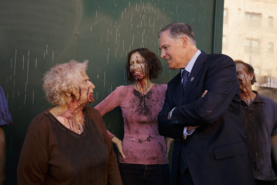 Governor Jay Inslee, right, speaks with zombie extra Susan Cleveland, left, as Brie Edwards looks on. - YOUNG KWAK