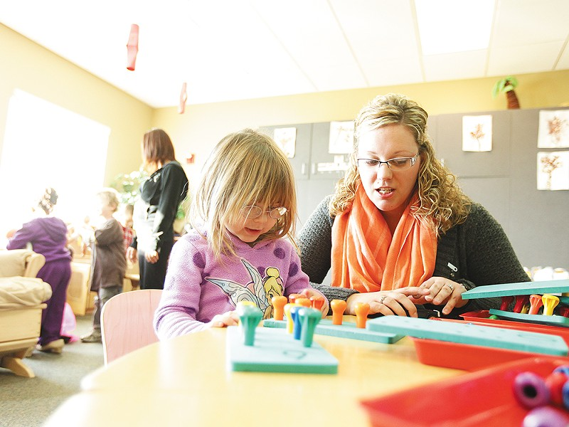 Head Start teacher Samantha Tuskan helps 3-year-old Tehya work on counting, color recognition and fine motor skills. - YOUNG KWAK