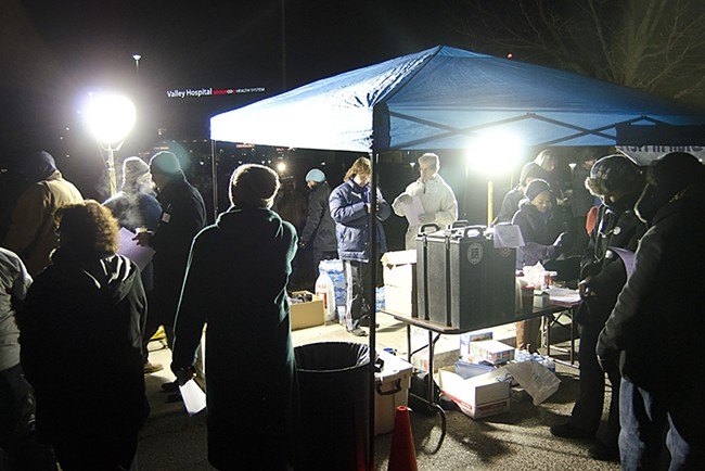 In predawn darkness, union members gather around a supply tent. - JACOB JONES