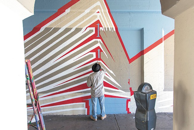 Jesse Santos helps paint the Wall Street mural. - MATT WEIGAND