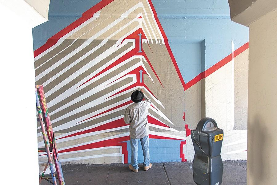 Jesse Santos helps paint the Wall Street mural. - MATT WEIGAND