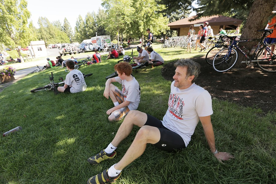 Jim Schmick, right, and his 13 year old son Henry rest after finishing the REI 21 Mile River Loop route. - YOUNG KWAK