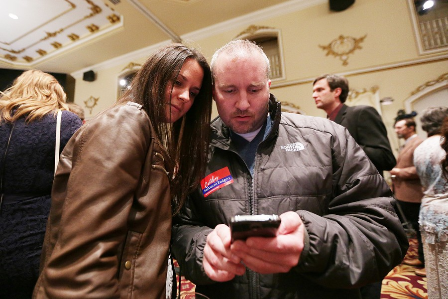 Jodey Miller, left, and her fiancé Michael Cannon monitor election results. - YOUNG KWAK