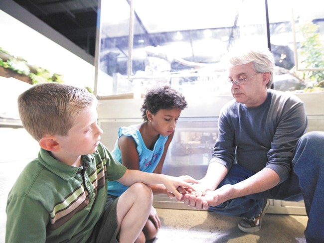 Jonas, left, and Olivia, center, pet a bearded dragon at Mobius Science Center. - YOUNG KWAK