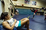 Julianna Peña, left, watches Ethan Rhoades, left, kick while sparring against Danial Varavin.