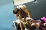 Julianna Peña, top, shows Anjela Pink, right, and Mariah Pierce how to perform a one armed short choke.