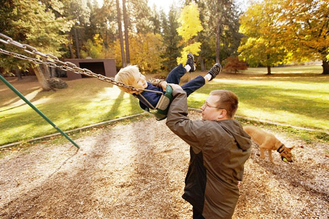 Justin Tolleson pushes his 2 year old son Derek on a swing as their 1 year old Rhodesian Ridgeback mix Tank plays nearby at Lincoln Park. - YOUNG KWAK