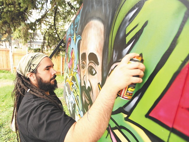 Justo Luis Rodriguez, founder of Upful Creations, works on a mural in his back yard. - YOUNG KWAK