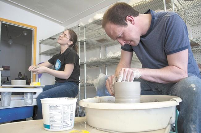 Karen Mannino and Nick Lowe throw clay on a pottery wheel at Urban Art Co-op. - SARAH WURTZ