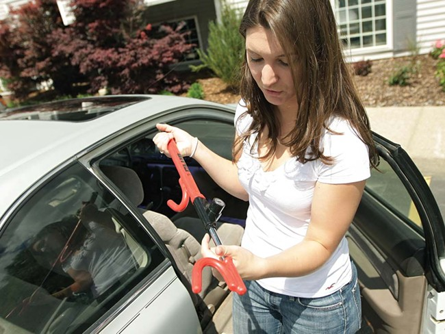 Karissa Mielke shows off 'The Club,' which she now uses after her car was stolen - twice. - YOUNG KWAK