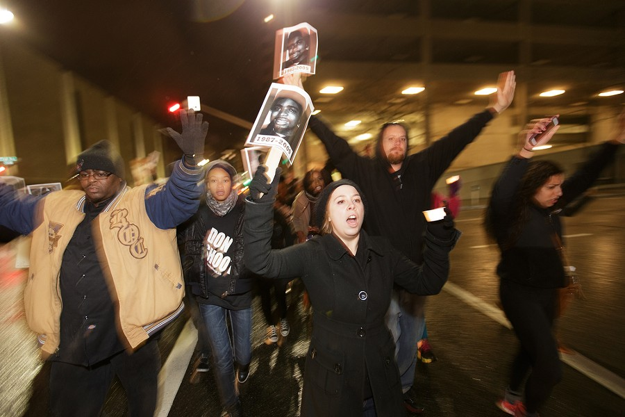 "Kellie Crawford, center, and others walk down W. 1st Ave., chanting ""hands up, don't shoot."" - YOUNG KWAK"