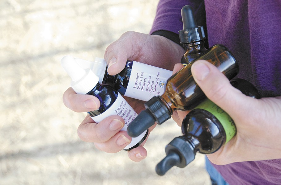 Kim Kalua juggles several tincture bottles for high-cannabidiol marijuana extract oil that the family has used to treat Koa's epilepsy. - JACOB JONES