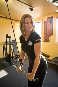 Kristin Bennett of H.I.T. Fitness does some tricep pushdowns in slow motion. - STEPHEN SCHLANGE