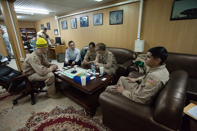 (Left to right) 376th Expeditionary Operations Group First Lieutenant Kevin Bishop, Airman First Class Amy Zemaitis, Captain Mike Dobbs, Captain Alex Denton and Senior Airman Mike Fernandez play Monopoly. - YOUNG KWAK