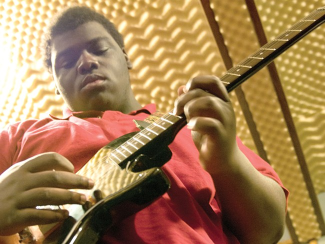 LeRon, 17, takes to the guitar during band practice at the Village Project studio. - AMY HUNTER