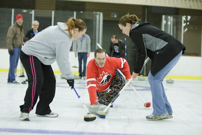 Lilac City Curling Club board member Dale Garraway, center, throws a rock as students Lanelle Ramey, left, and Christina Akinlosotu sweep. - YOUNG KWAK