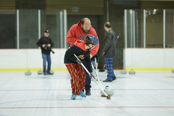 Lilac City Curling Club President Eric Thompson and his 10-year-old son and member Ethan sweep. - YOUNG KWAK