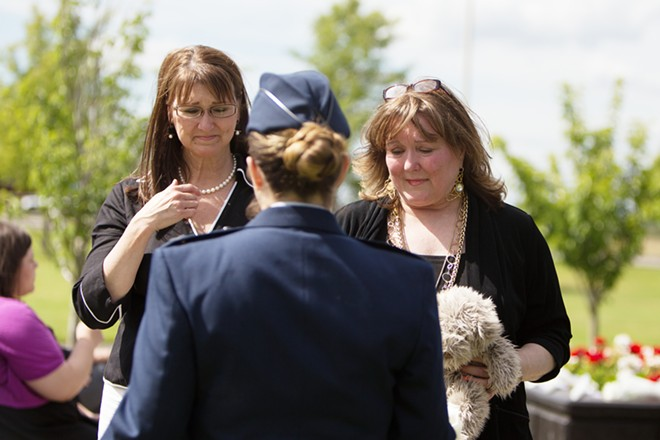 Lori Payton, left, and Roni Uyeda accept a white rose from Captain Paula Clark on behalf of Michelle Sigman's unborn daughter, Taylor, who died in the womb after her mother was injured during the shooting. Payton and Uyeda are daughters of Eva Walch, who was wounded while protecting Sigman's son, James, from the gunman. - YOUNG KWAK