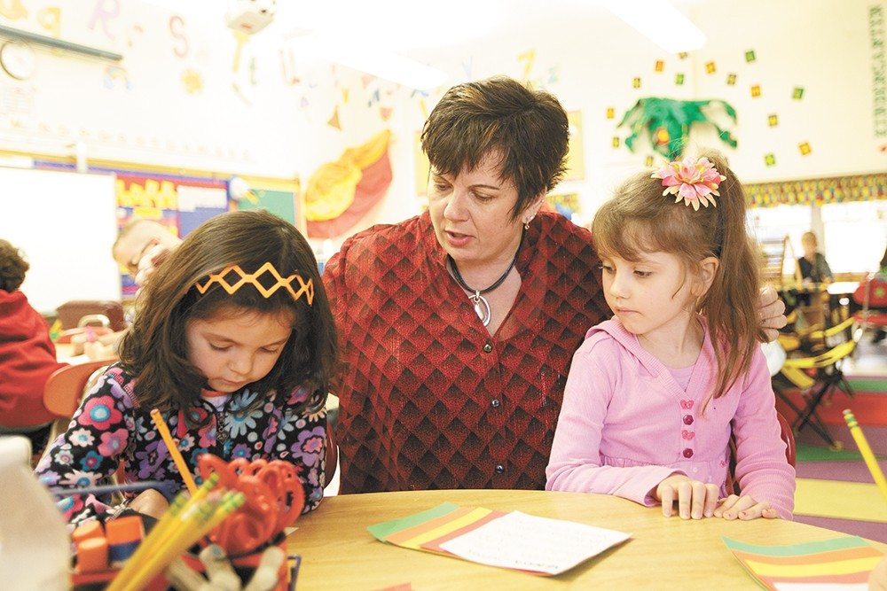 Madison Elementary kindergarten teacher Bambi Howe helps 5-year-olds Olivia Allen, left, and Vanessa Syrros with their writing assignments. - YOUNG KWAK