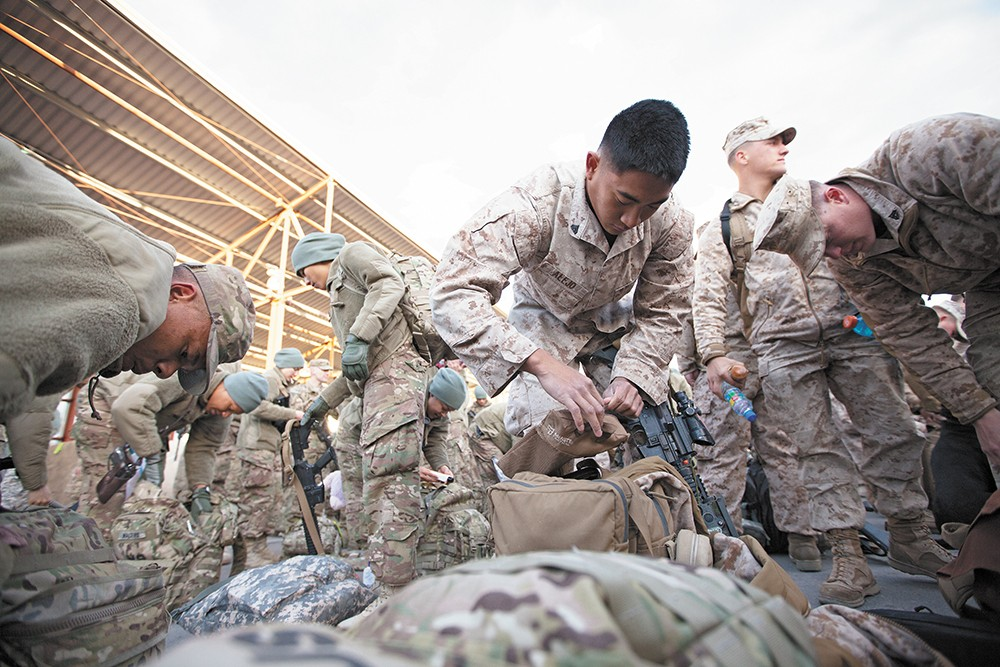 Marine Cpl. Arnold Alejo goes through his luggage, making sure he's ready for his trip home. - YOUNG KWAK